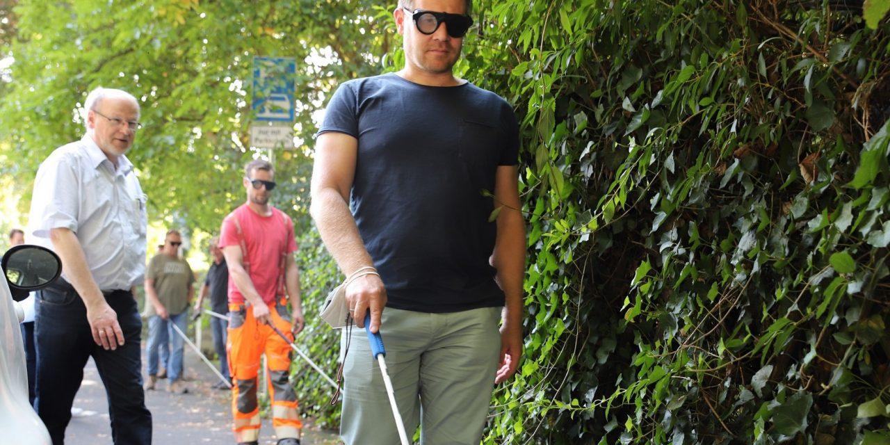 Mit Augenbinde und Blindenstock auf der Baustelle